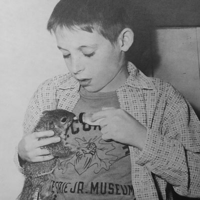 Vintage photo of boy feeding baby squirrel